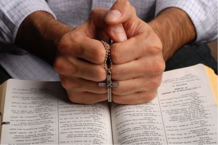 Man's Hands Holding Cross Over Bible